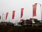 Флаги с логотипом Макдональдс на уличных флагштоках
